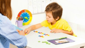 Concentrated boy putting colorful coins in order during developing game with his mother sitting at the table indoors